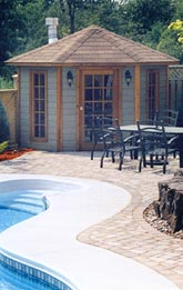 pool house in corner of pool deck showing pool heater chimney stack and coach lights with patio set in foreground