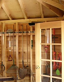 garden shed interior showing spruce framing, cedar French door and garden tools neatly arranged.