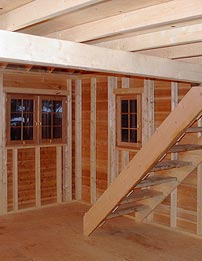 image of inside of large cabin kit looking out front windows with fixed stairs leading to a sleeping loft overhead